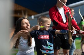 A mother helps her son aim at the target at the practice area of the 3D archery course.  | © Hinterramskogler