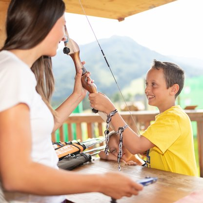 A young boy renting a bow at the 3D archery course on Wurbauerkogel.