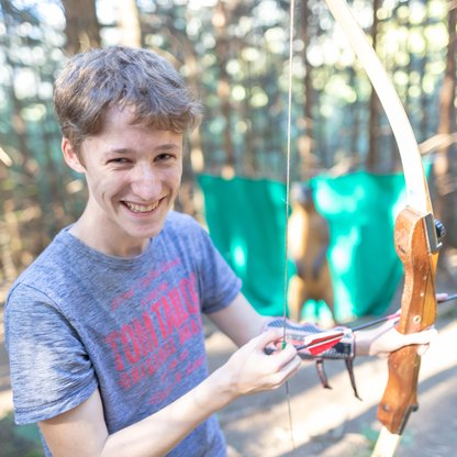 Boy laughing while trying to pull the bowstring.  | © Hinterramskogler