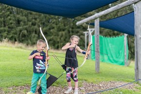 Two kids practicing their skills with bow and arrow at the practice area on Wurbauerkogel.  | © Hinterramskogler