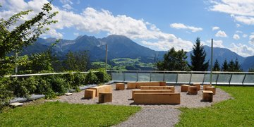 A cosy seating area made of wood invites guests on Wurbauerkogel to have a seat.