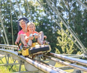 A mother and daughter on a two-person sled on the Alpine Coaster.  | © Hinterramskogler