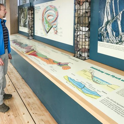 "A visitor looking at the big illustrations at the ""The fascinating world of rocks"" exhibition.  