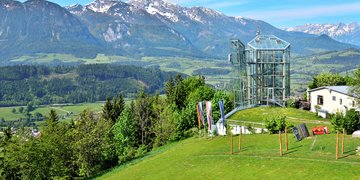 The glass Panorama Tower on Wurbauerkogel in spring with the mountains in the background.