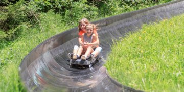 Two girls leaning into the curve on the summer toboggan run on Wurbauerkogel.  | © Hinterramskogler