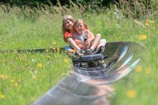 Two girls enjoy a speedy ride down the summer toboggan run on Wurbauerkogel.  | © Hinterramskogler