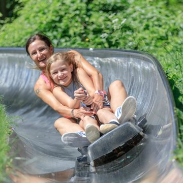 A woman and her daughter swoosh downhill on the summer toboggan run on Wurbauerkogel. | © Hinterramskogler
